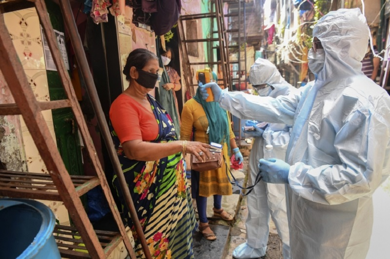 Medical staff wearing personal protective equipment (PPE) conduct a door-to-door medical screening inside the Dharavi slums. ― AFP pic