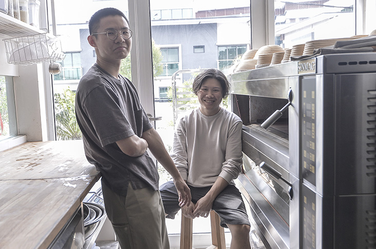 One Half's Keith Koay (standing) and Artisan Roastery's Joey Mah (seated) have opened a bakery together — Dou Dou Bake. — Pictures by Shafwan Zaidon and Miera Zulyana