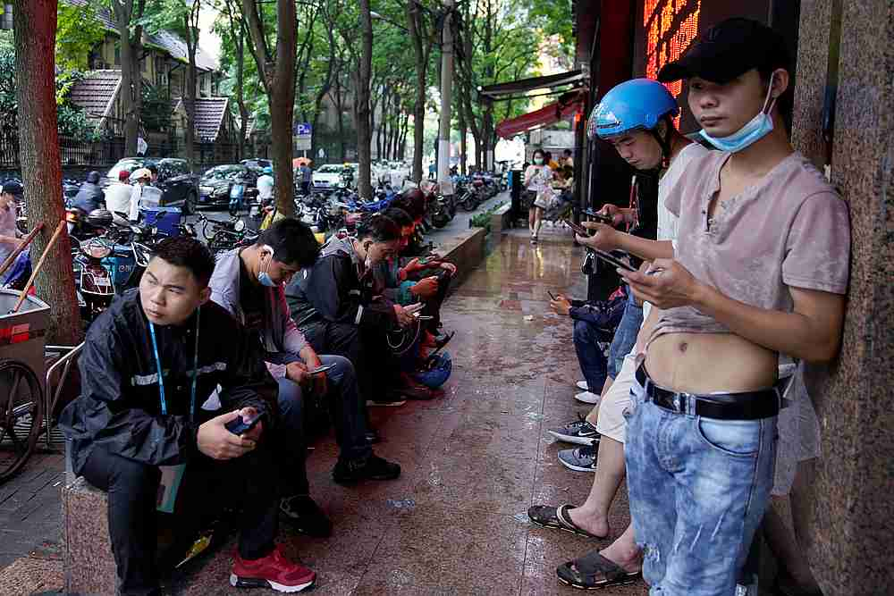 Delivery workers wait for online orders on a street in Shanghai, following the Covid-19 outbreak, China July 13, 2020. — Reuters pic