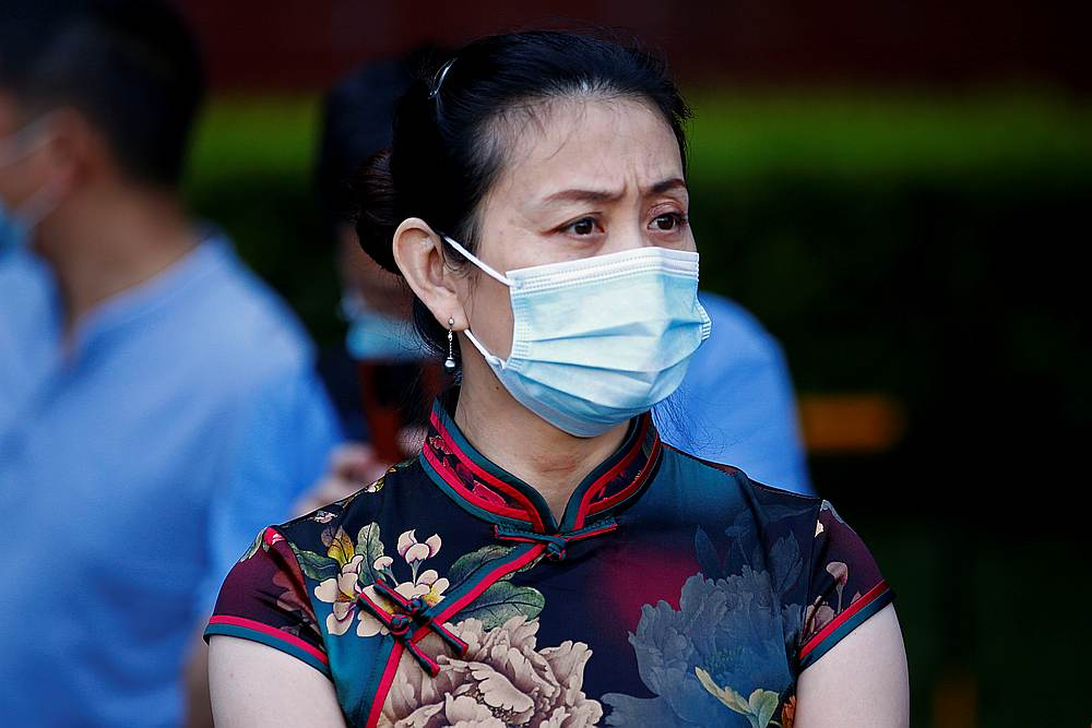 A woman wearing a face mask waits outside a high school as students take part in the annual national college entrance exam or 'gaokao,' in Beijing, China July 7, 2020. — Reuters pic