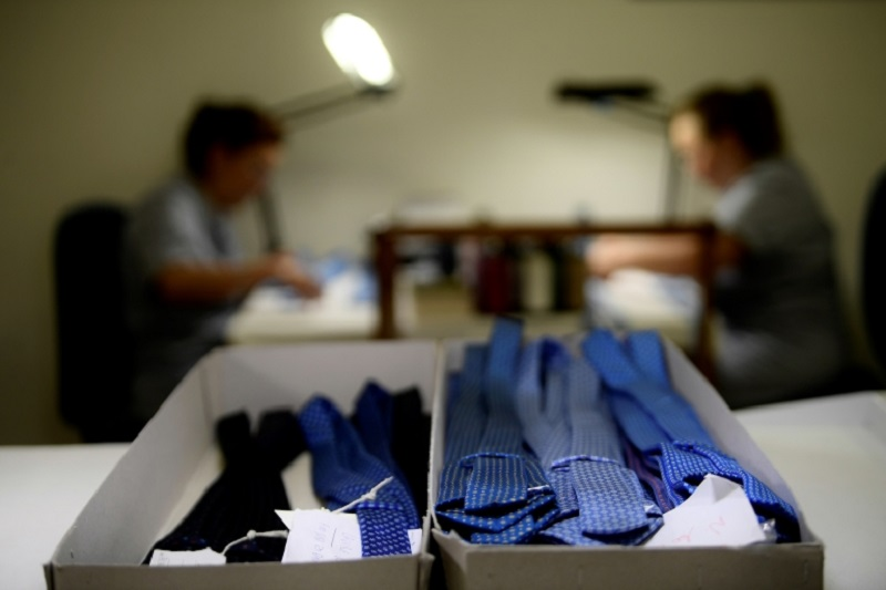 Finished bundles of ties sit in boxes as seamstresses work in the workshop of the 'E. Marinella' shirt and tie makers familybusiness in Naples. ― AFP pic