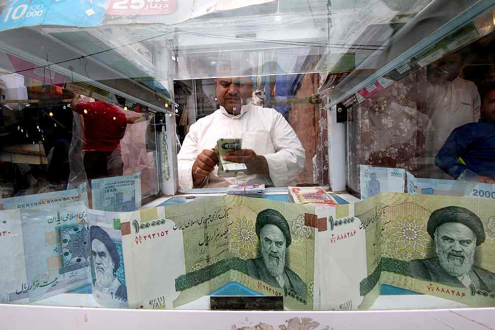 A man counts Iranian rials at a currency exchange shop, before the start of the US sanctions on Tehran, in Basra, Iraq November 3, 2018.  — Reuters pic