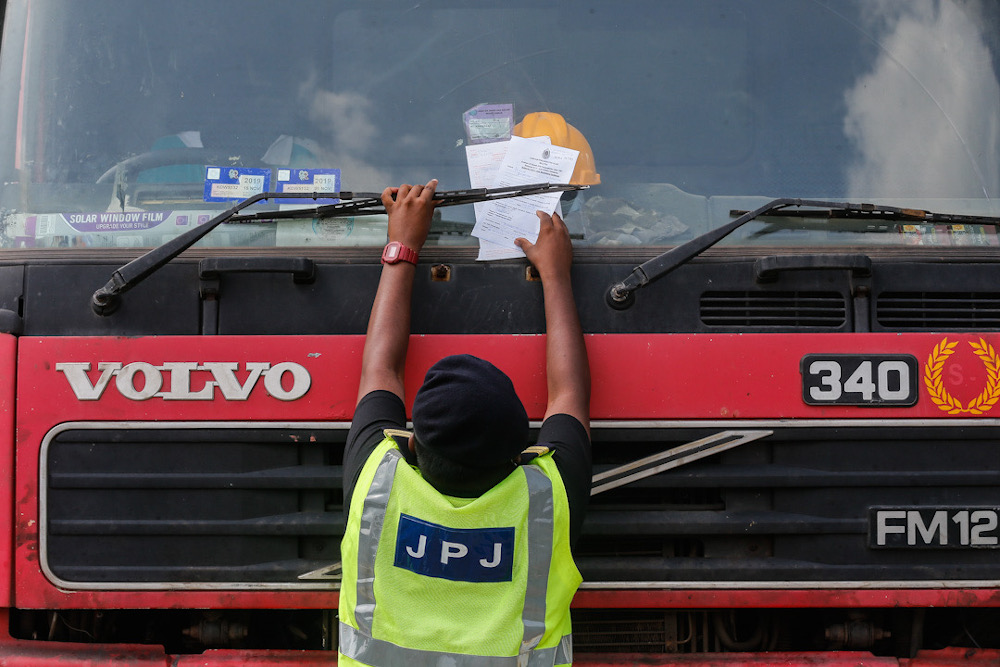 A Road Transport Department officer places a summons on a lorry believed to be breaking the rules on transporting goods at Sungai Dua, Penang, July 21, 2020. — Picture by Sayuti Zainudin
