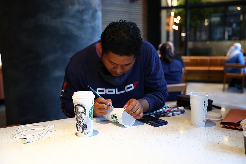 Luqman Hakim in his zone as he draws portraits on various Starbucks cups. His medium extends to paper cups, reusable cups and even canvas. — Picture courtesy of Starbucks Malaysia