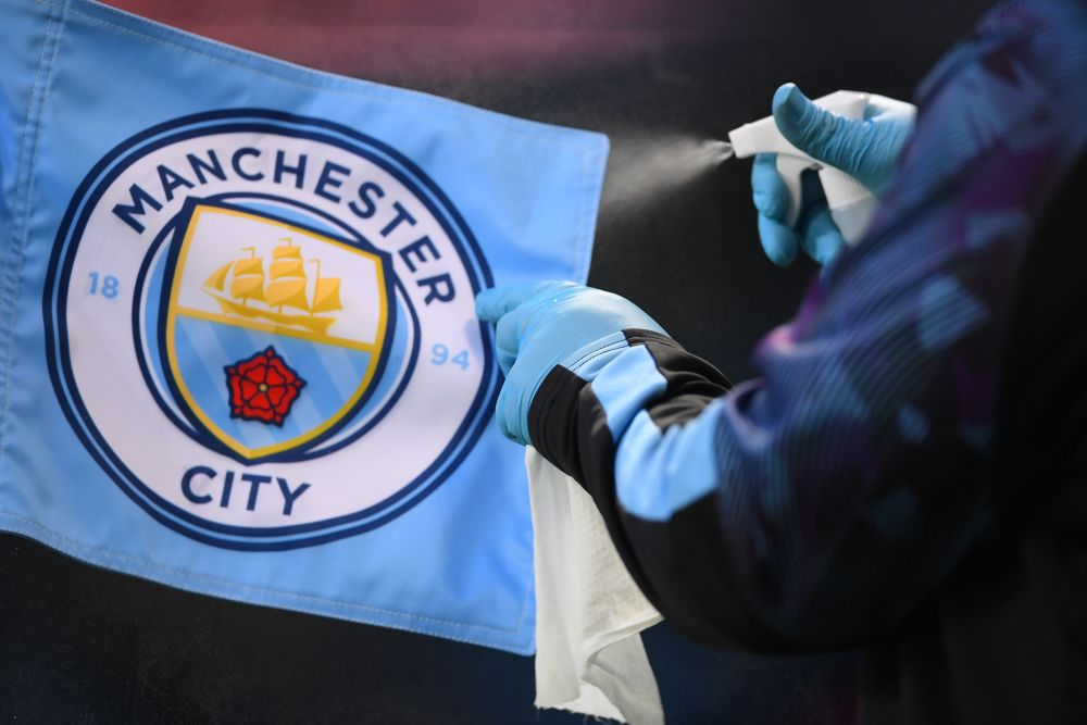 A staff member disinfects the corner flag during Manchester City's Premier League match against Liverpool at the Etihad Stadium, Manchester July 3, 2020. — Reuters pic