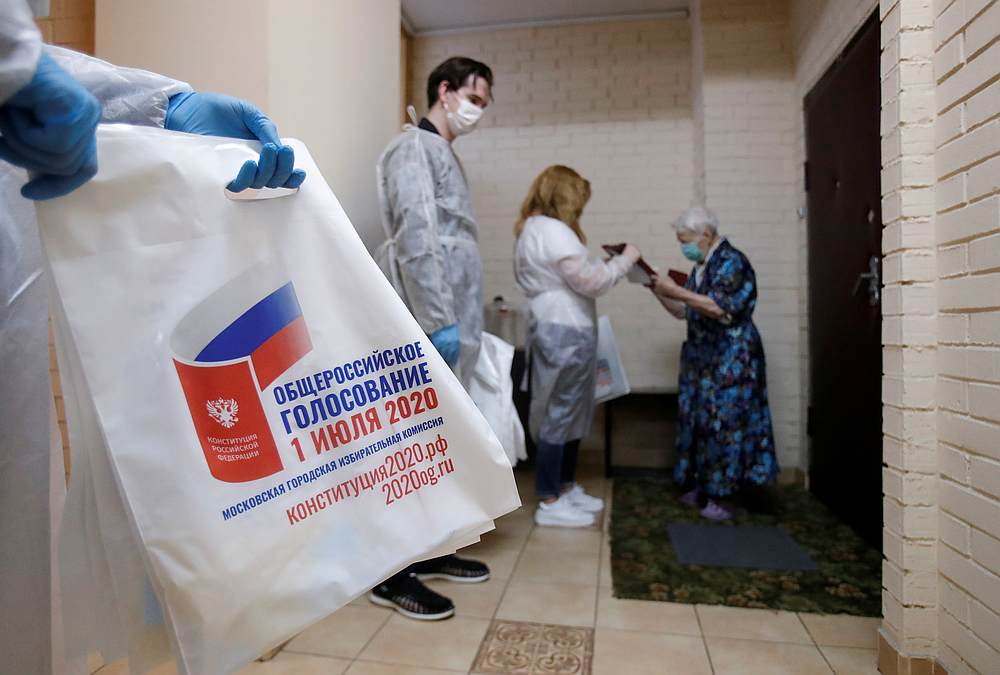 Members of an electoral commission wearing protective equipment visit local residents on the last day of a weeklong nationwide vote on constitutional reforms in Moscow, Russia July 1, 2020. — Reuters pic