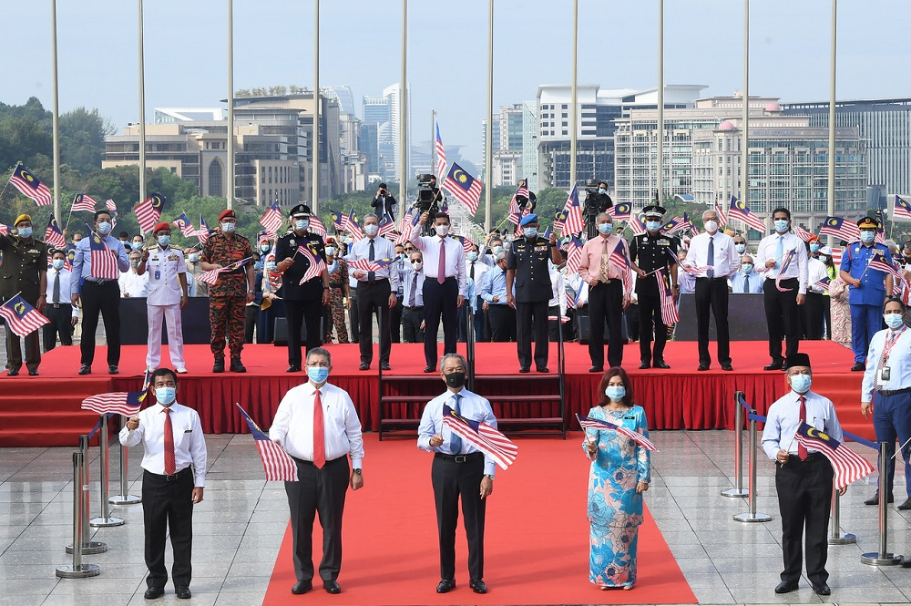Prime Minister Tan Sri Muhyiddin Yassin raises the Jalur Gemilang during the launch of the National Month and Fly the Jalur Gemilang 2020 Campaign at Dataran Perdana in Putrajaya June 28, 2020. ― Bernama pic