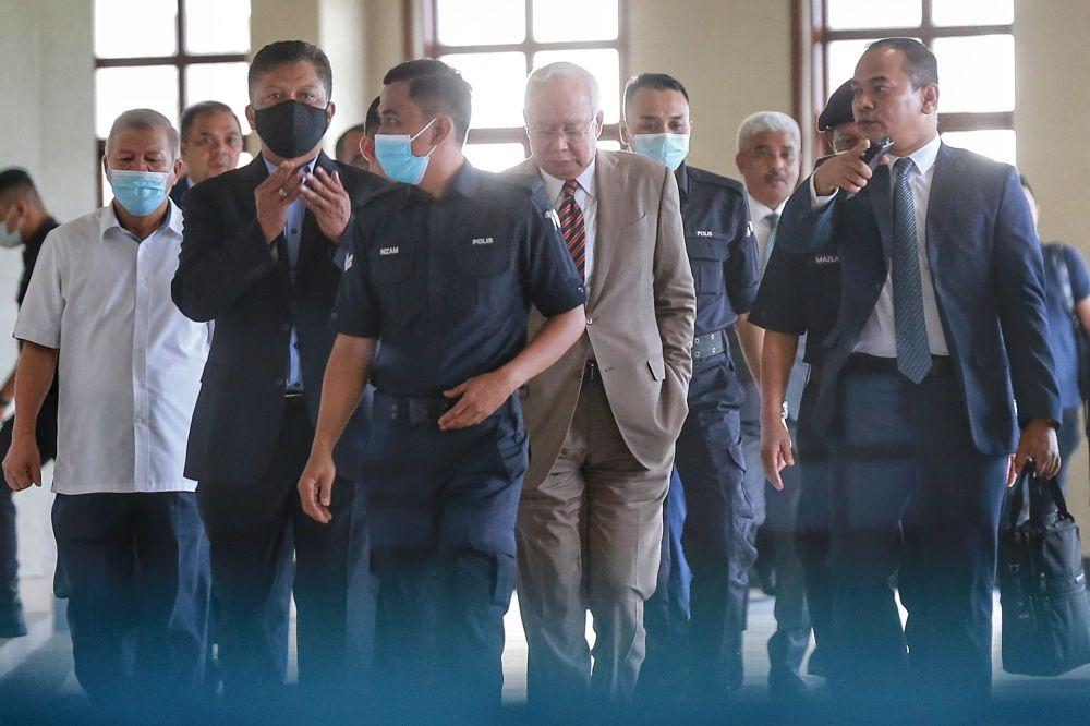 Datuk Seri Najib Razak (centre) is escorted by police officers at the Kuala Lumpur Court Complex July 28, 2020. ― Picture by Ahmad Zamzahuri