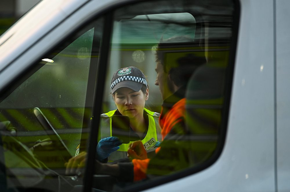 A NSW police officer checks a driver's permit as he crosses from the state of Victoria into New South Wales (NSW) at a border check point in Albury, New South Wales, Australia July 8, 2020. — AAP Image via Reuters