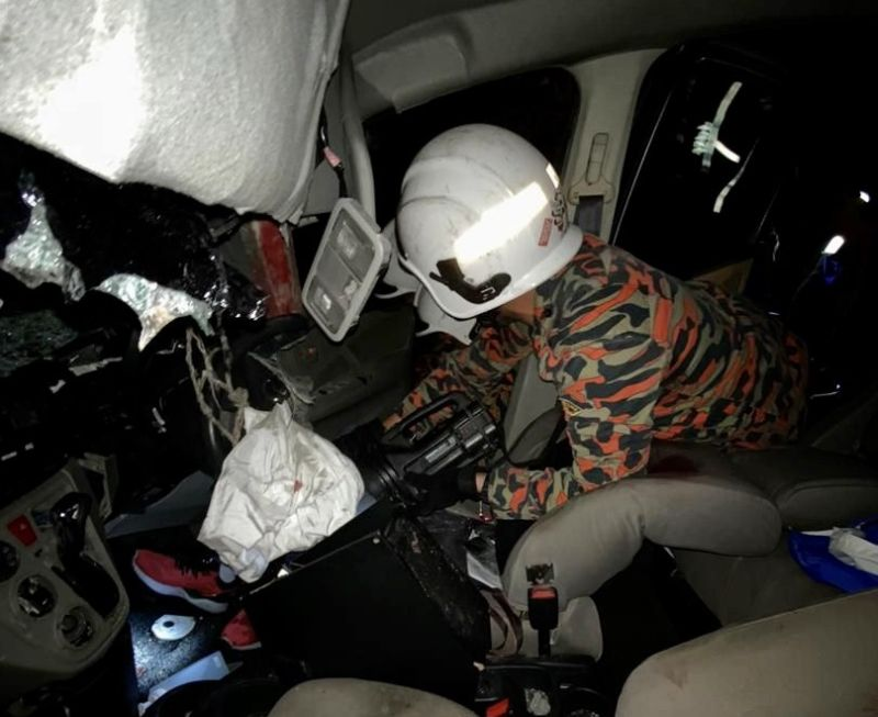 A Fire and Rescue Dept personnel attempts to extract victims from the wreckage following an accident involving a motorcycle, lorry and three cars along the North-South Expressway last night. — Picture courtesy of the Johor Fire and Rescue Department