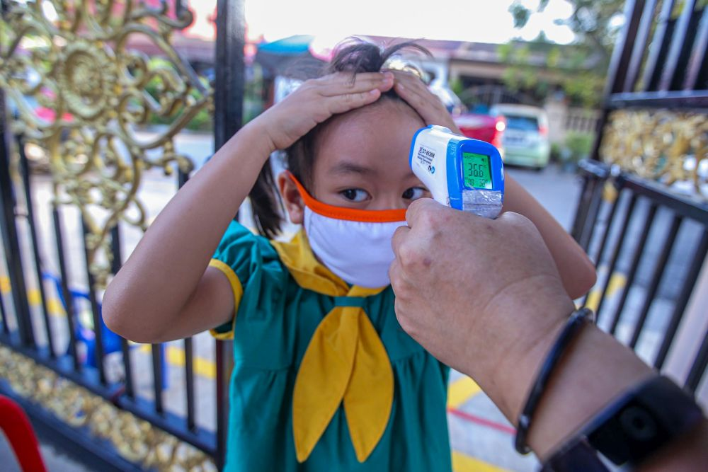 A preschooler has her temperature checked on her first day back at school in Kuala Lumpur July 1, 2020. — Picture by Hari Anggara