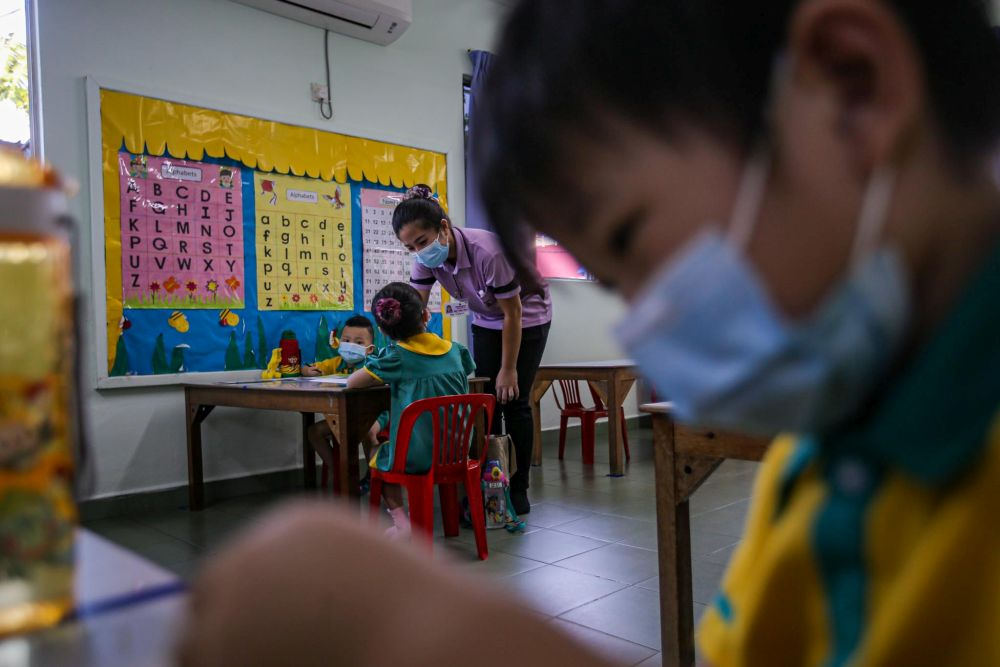 Preschoolers are seated accordingly to maintain social distancing while a teacher conducts a class at Mayter Kindergarten in Cheras in this file picture taken on July 1, 2020. — Picture by Hari Anggara