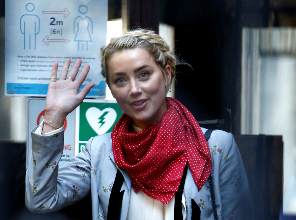 Actor Amber Heard waves as she arrives at the High Court in London July 21, 2020. — Reuters pic