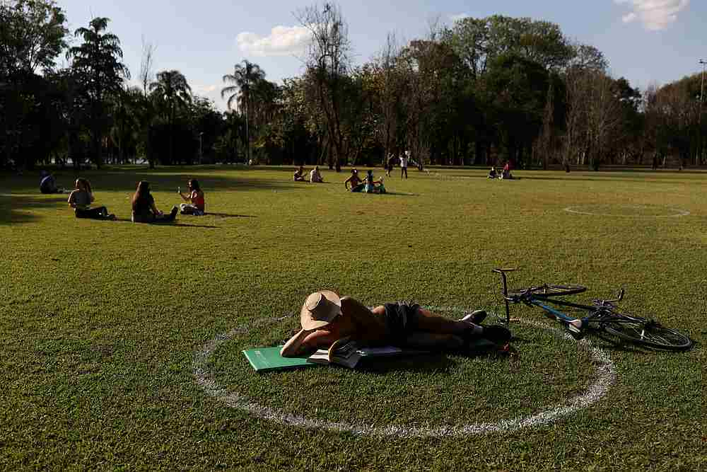 A man reads as he lies in a field where circles were painted to help visitors maintain social distancing at Ibirapuera Park in Sao Paulo, Brazil July 13, 2020. — Reuters pic