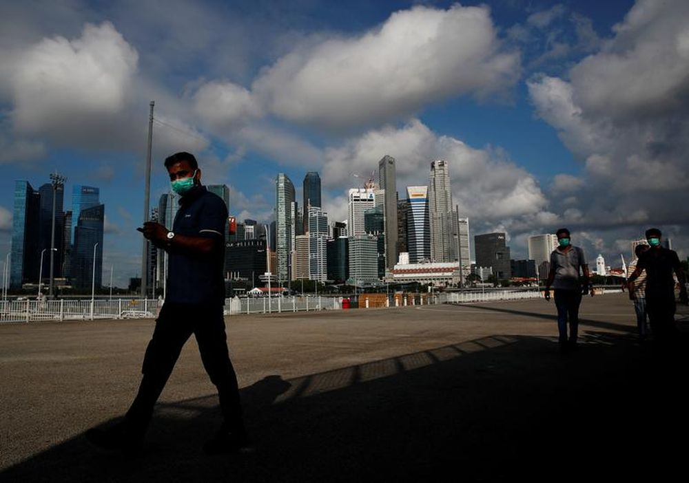 Essential workers wearing face masks walk past the skyline of the central business district outside a regional screening centre amid the coronavirus disease outbreak in Singapore June 9, 2020. — Reuters pic