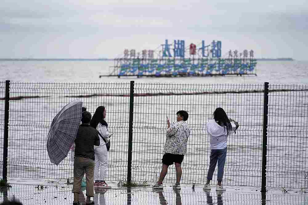 People stand by the Tai Lake, which has flooded its banks following heavy rainfall, in Huzhou, Zhejiang province, China July 15, 2020. — Reuters pic