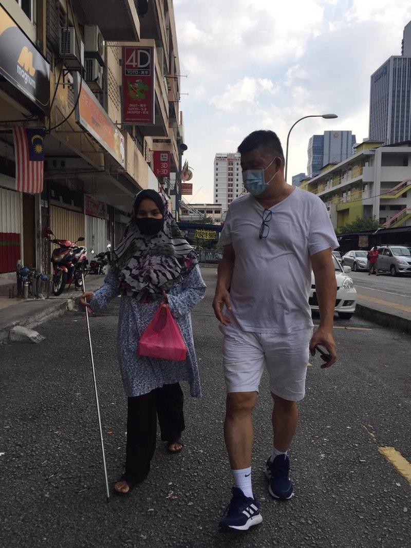 在行动限制令期间,关志庭(右)协助视觉障碍女士送上食物。-图摘自关志庭脸书-
