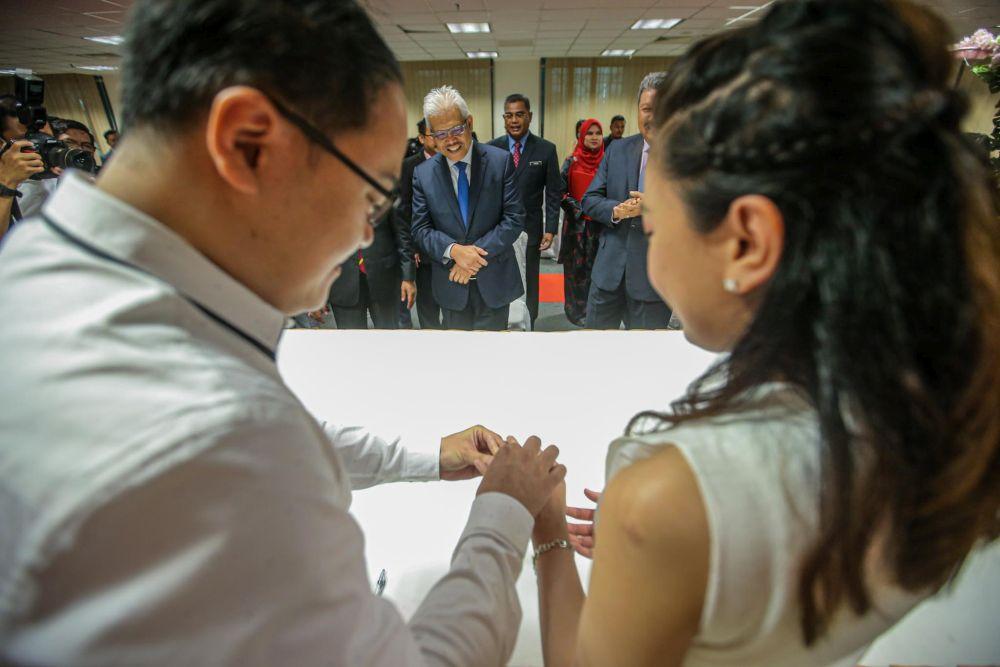 Home Minister Datuk Seri Hamzah Zainudin witnesses the wedding registration of Chinese couple Wong Wai Ying and Ng Mung Hong at the National Registration Department in Putrajaya July 20, 2020. — Picture by Hari Anggara