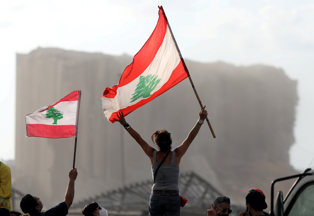 Demonstrators wave Lebanese flags during protests near the site of a blast at Beirut's port area, Lebanon August 11, 2020. — Reuters pic