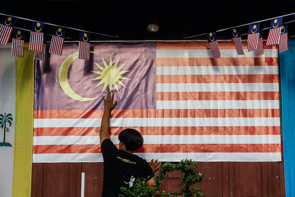 A man places a large Malaysian flag in front of a house at Kg Perlis, Balik Pulau August 15, 2020. — Picture by Sayuti Zainudin