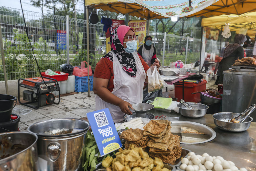 A vendor displays an e-wallet acceptance board at her stall in Setapak August 15, 2020.
