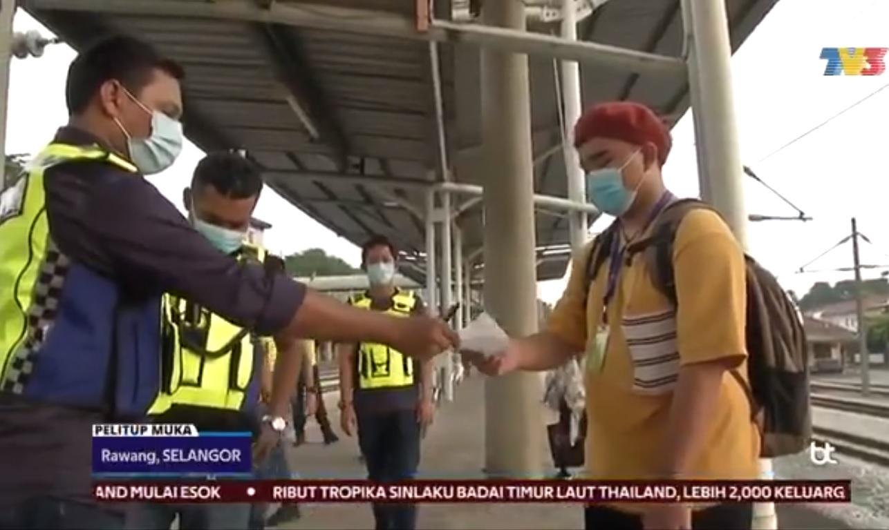 在KTM站的青年(右)因用手拉下口罩数秒而遭执法警员开罚单。-图撷取自视频-
