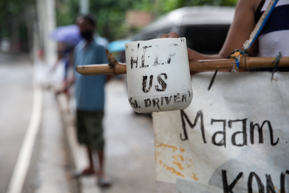 A plastic cup with the words 'help us' is held by a jeepney driver who lost his livelihood amid the coronavirus disease (Covid-19) outbreak, on a roadside in Quezon City, Metro Manila, Philippines, July 30, 2020. — Reuters pic