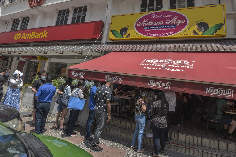 People are seen disregarding social distancing rules while waiting at the entrance of Sri Nirwana Maju banana leaf restaurant in Bangsar August 1, 2020. — Picture by Shafwan Zaidon