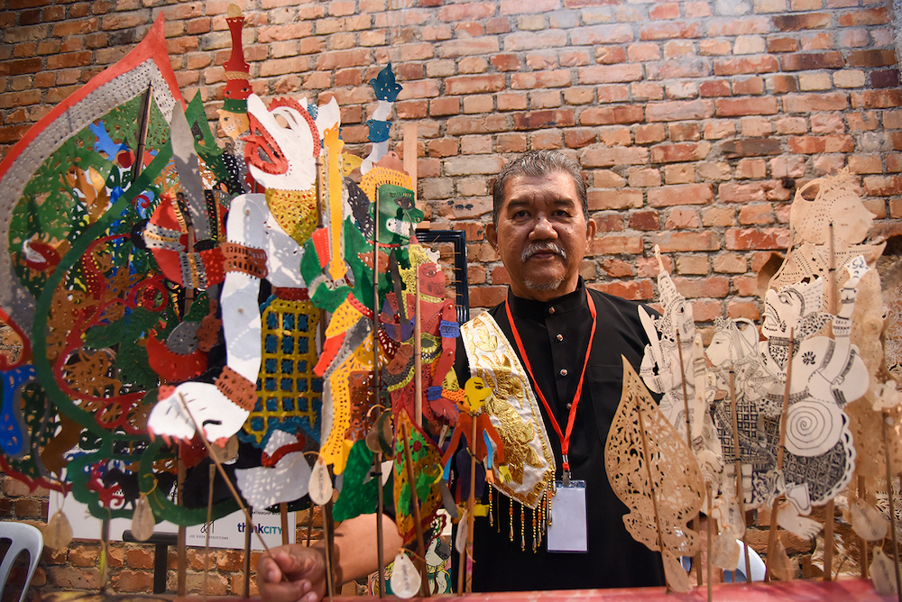 Mohd Jufry Yusoff with the 'wayang kulit' puppets made by him.