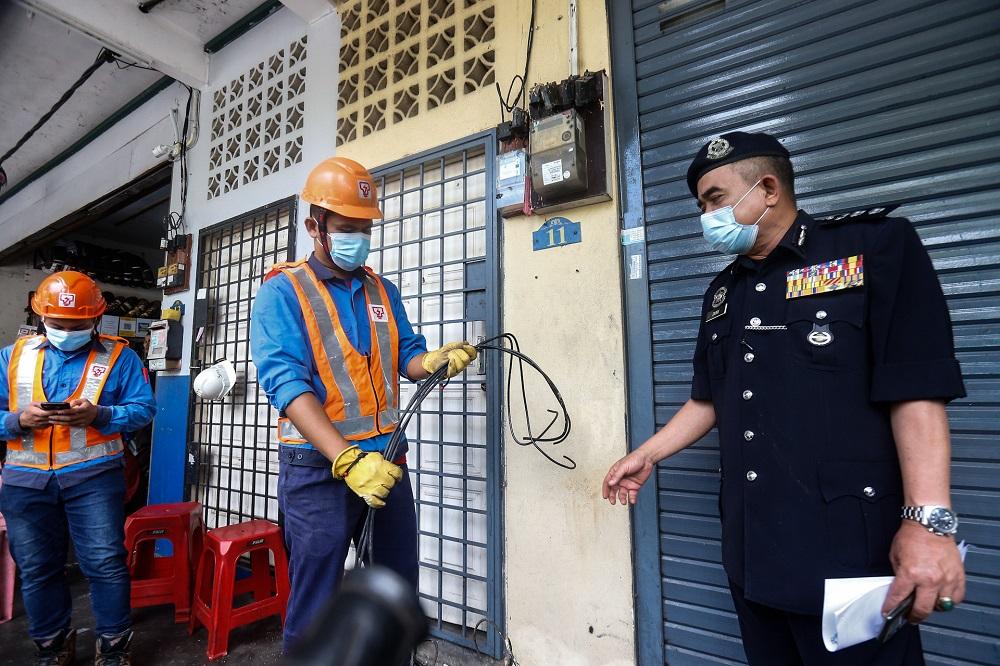 Tenaga National Berhad personnel cut the main power line to a shoplot that runs an illegal gambling den here at Bertam Putra, Kepala Batas August 13, 2020. —  Picture by Sayuti Zainudin