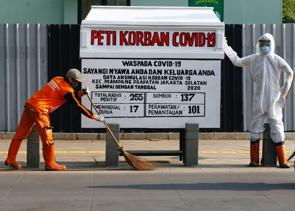 A worker sweeps near a mock coffin and a dummy dressed in a personal protective suit to resemble a health worker, in a public area to warn people about the dangers of the coronavirus disease in Jakarta, Indonesia, August 19, 2020. — Reuters pic