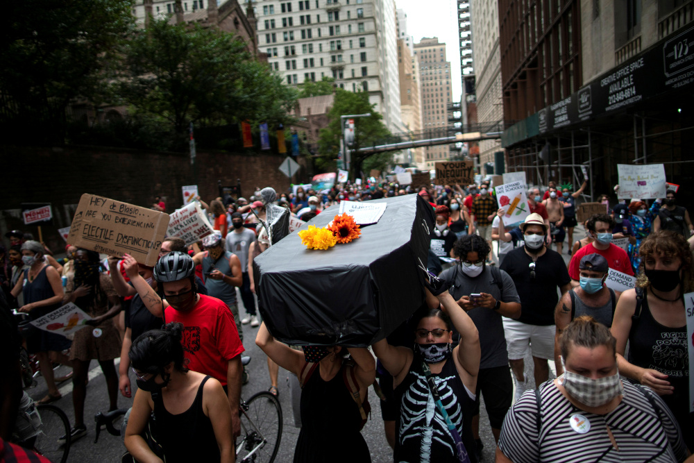 People carry a fake coffin as symbol of a student dead by Covid-19 as they take part in a march and rally during the National Day of Resistance to schools re-opening in New York, US, August 3, 2020. — Reuters pic