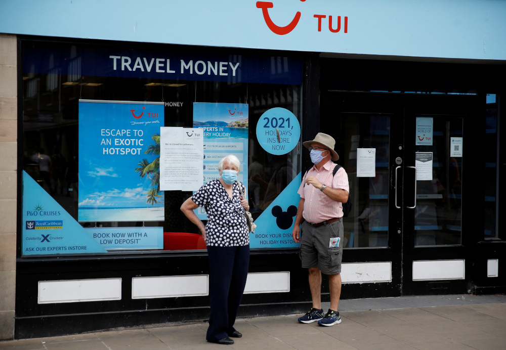 People wear face coverings as they stand outside a TUI travel agents shop following the outbreak of the coronavirus disease in Chester, Britain, August 10, 2020. — Reuters pic