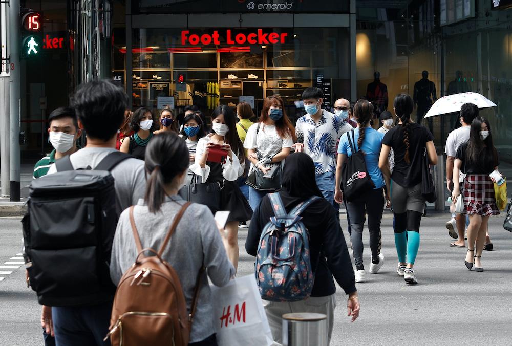 Pembeli yang mengenakan masker pelindung wajah menyeberang jalan di distrik perbelanjaan Orchard Road Singapura selama wabah penyakit virus korona di Singapura, 17 Agustus 2020. - Foto Reuters