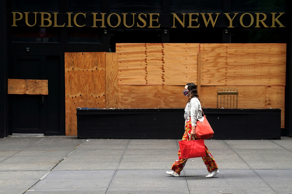 A woman walks past a shuttered bar following the coronavirus disease outbreak in the Manhattan borough of New York City, New York, US, August 7, 2020. — Reuters pic
