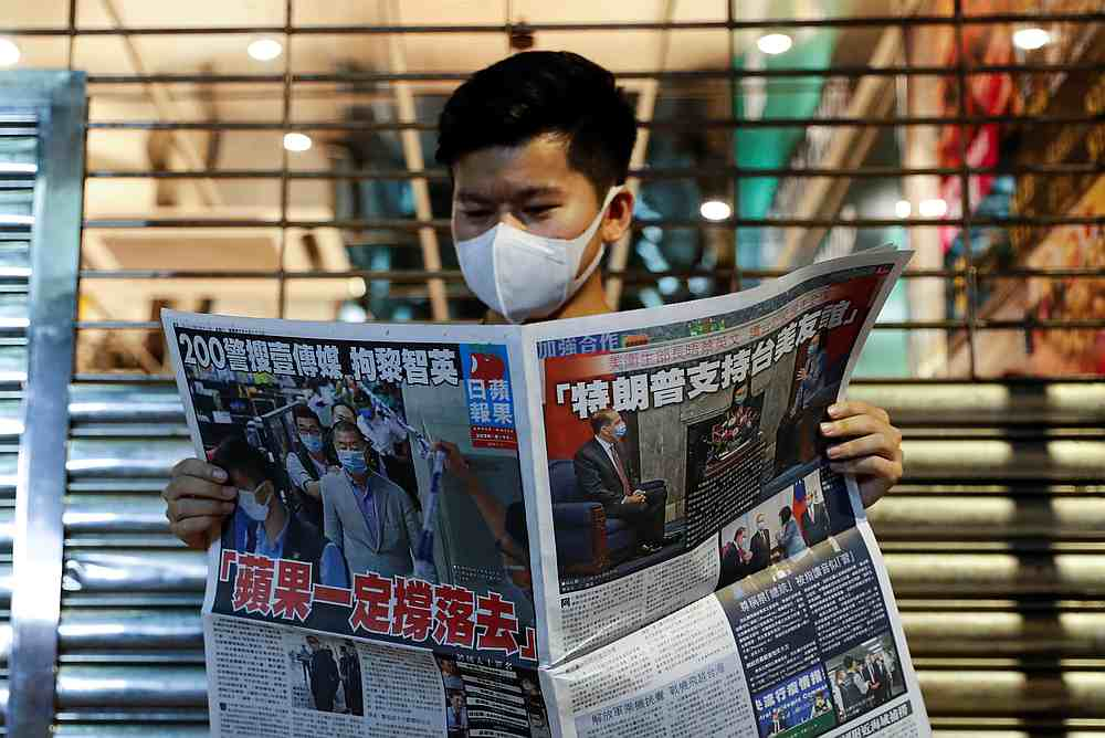 A supporter of Apple Daily newspaper, reads a copy of the newspaper to support media mogul Jimmy Lai Chee-ying, founder of Apple Daily after he was arrested in Hong Kong August 11, 2020. — Reuters pic