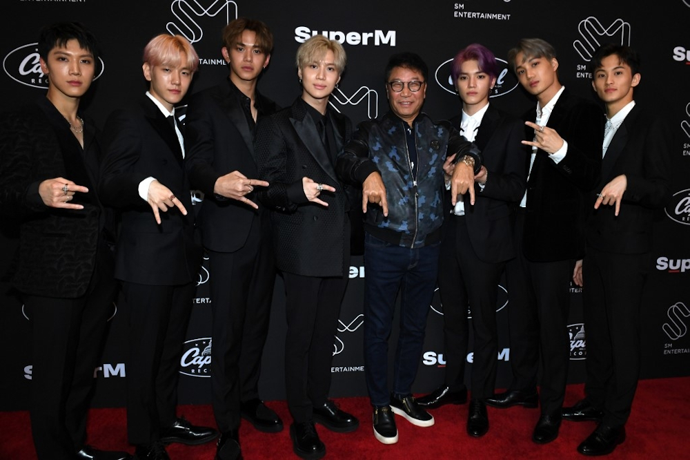 Members of K-pop supergroup SuperM posing with South Korean record producer Lee Soo-man (4th right) during a press conference at the Capitol Records Tower in Hollywood on October 3, 2019. — AFP pic