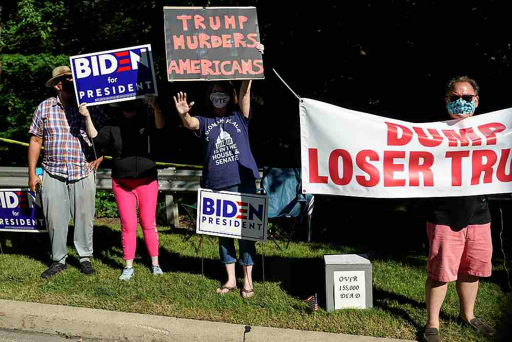 Supporters of Democrat Joe Biden hold up signs as US President Donald Trump arrives at the Shoreby Yacht Club in Bratenahl, Ohio August 6, 2020. — Reuters pic