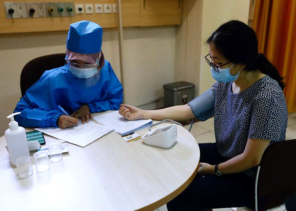 A healthcare worker checks the tension of a volunteer during a simulation for coronavirus vaccine clinical trials next week at Padjadjaran University in Bandung, Indonesia August 6, 2020. — Reuters pic