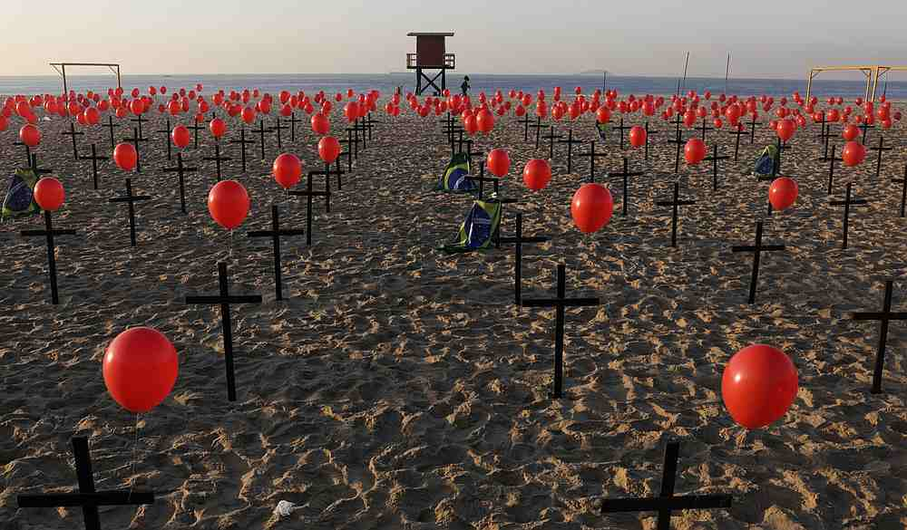 A woman jogs past crosses and balloons placed by members of the NGO Rio de Paz in tribute to the one hundred thousand Covid-19 deaths in Brazil, at the Copacabana beach in Rio de Janeiro August 8, 2020. — Reuters pic
