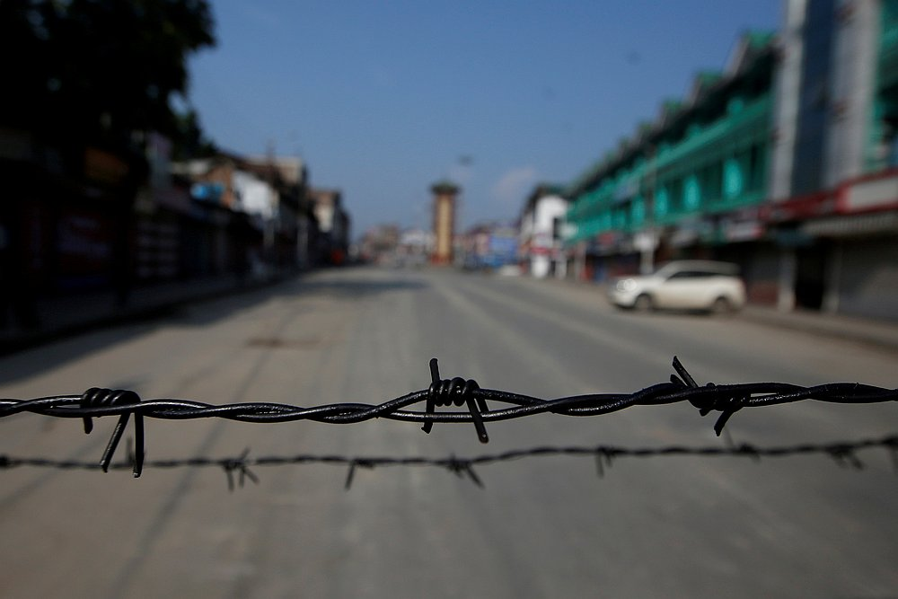 Barbed wire is seen laid on a deserted road during restrictions in Srinagar, August 5, 2019. — Reuters pic