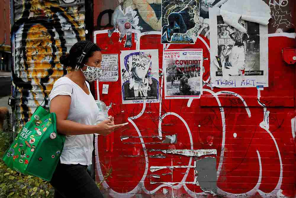 A woman wearing a protective face mask walks past graffiti amid the spread of Covid-19 in Brooklyn, New York August 4, 2020. — Reuters pic