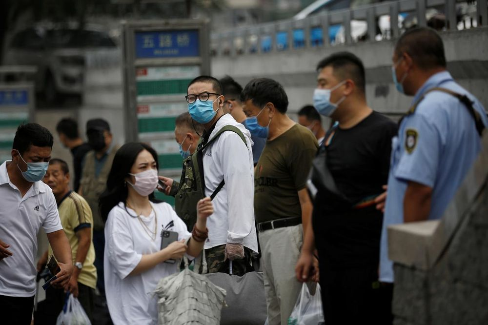 People wearing face masks wait at a bus stop during morning rush hour, following the outbreak of the coronavirus disease (Covid-19), in Beijing, China July 13, 2020. — Reuters pic