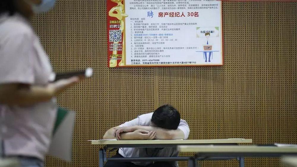 A job seeker takes a break at a recruitment fair in Zhengzhou, China. Young graduates face a tough employment market. — AFP pic