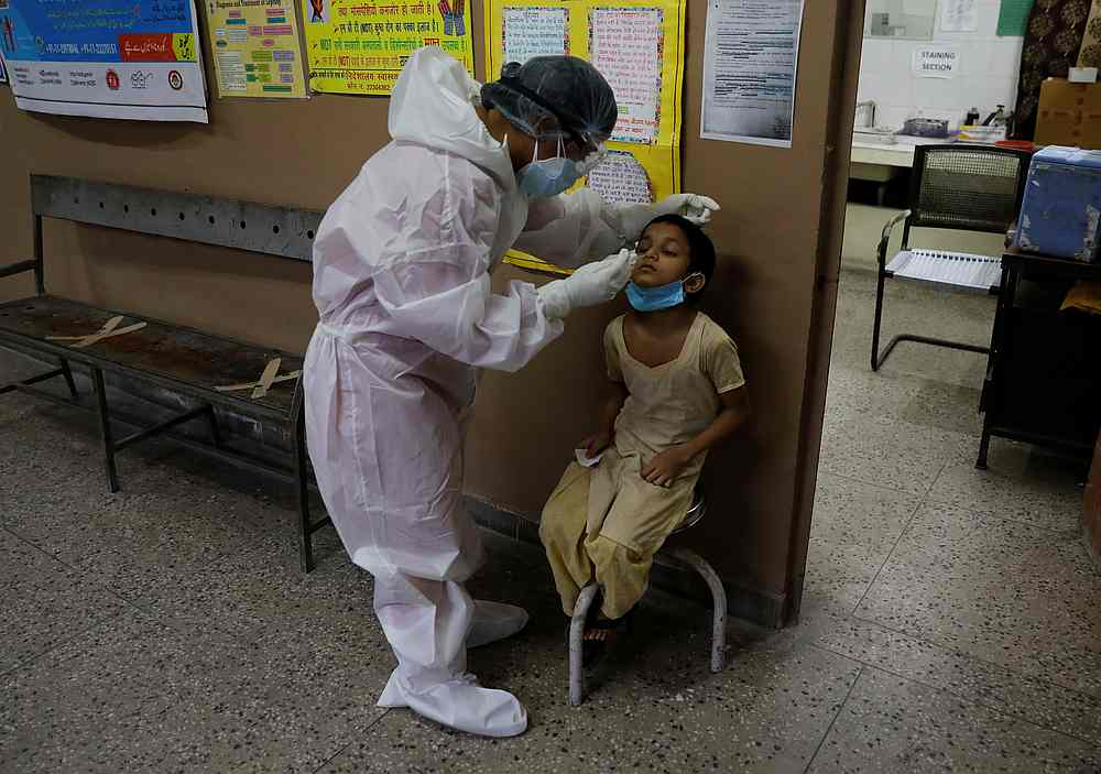 A health worker in personal protective equipment (PPE) collects a sample using a swab from a person at a local health centre to test for Covid-19 in New Delhi, India August 7, 2020. — Reuters pic