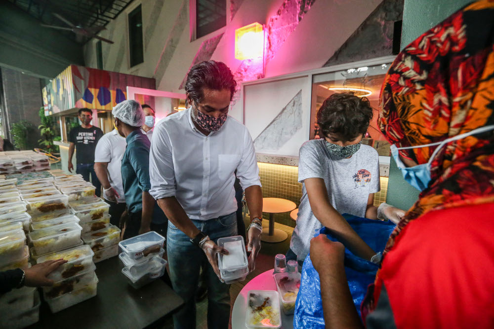 Minister of Science, Technology, and Innovation Khairy Jamaluddin hands over meals for distribution during the ECM Libra Foundation and Pertiwi Covid-19 Food Aid Programme in Kuala Lumpur August 14, 2020. — Picture by Firdaus Latif