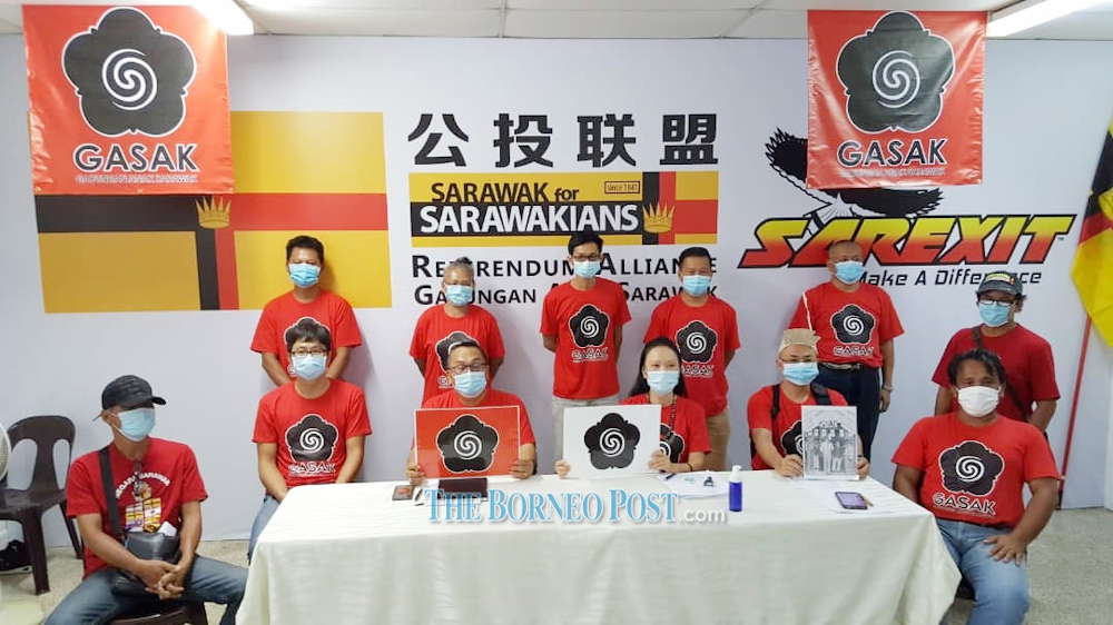 Bobby (seated, 3rd left) and Soo (seated, 3rd right) show the logo to be submitted by Gasak. — Picture by Borneo Post