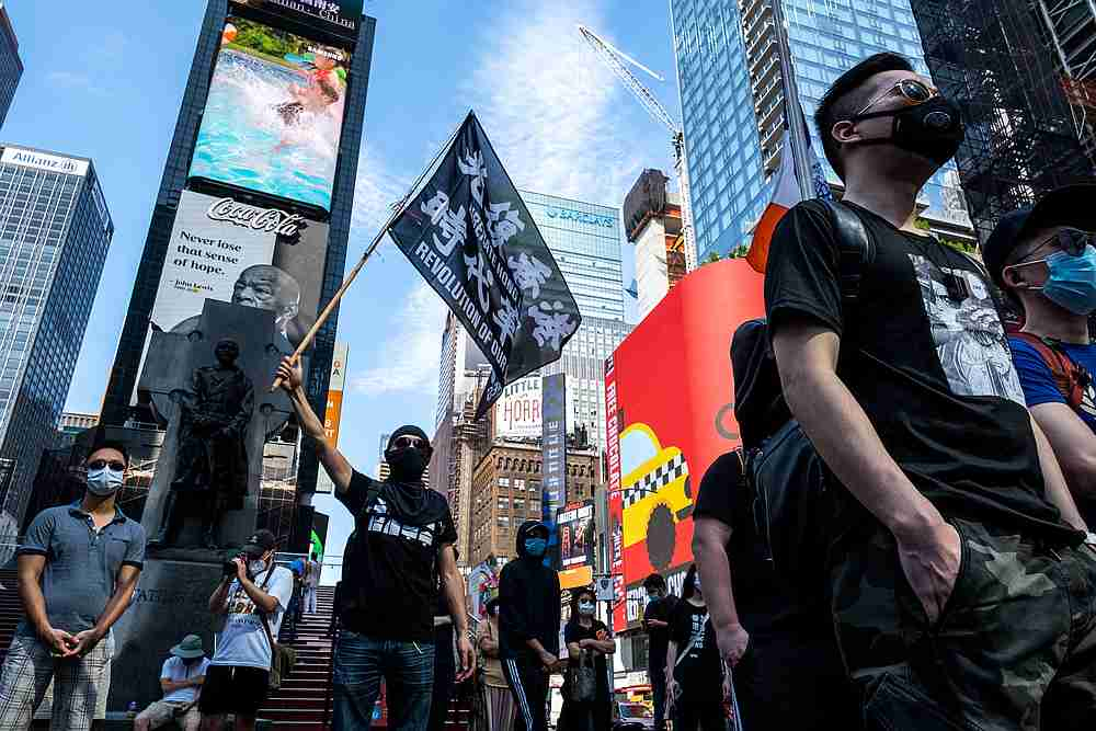 Protester supporting Hong Kong's pro-democracy movement wearing protective mask holds a flag as they attend the Delay No More, Democracy march in Times Square, New York August 2, 2020. — Reuters pic