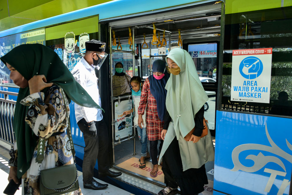 A bus crew member wearing a face shield as a preventive measure to curb the spread of the Covid-19 coronavirus helps passengers get off a bus in Banda Aceh August 22, 2020. — AFP pic