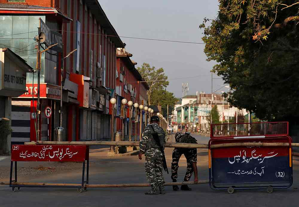 Indian Central Reserve Police Force officers put up a roadblock on an empty street during a lockdown on the first anniversary of the revocation of Kashmir's autonomy, in Srinagar August 5, 2020. — Reuters pic